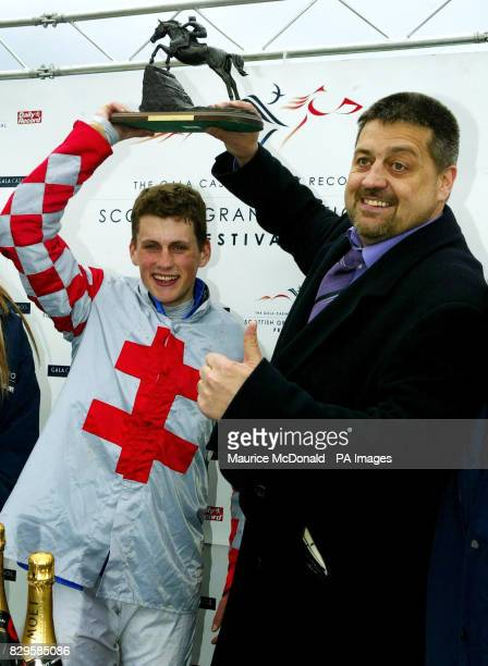 Jockey Keith Mercer and owner Chris Massie celebrate with the trophy after Joes Edge won the Gala Casinos Daily Record Scottish Grand National