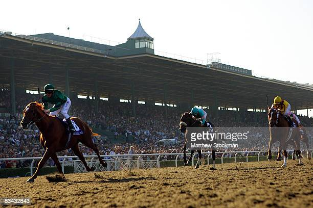 Jockey Lanfranco Dettori atop Raven's Pass crosses the finish line ahead of Mike Smith atop Tiago and Robby Albarado atop Curlin to win the Breeders'...