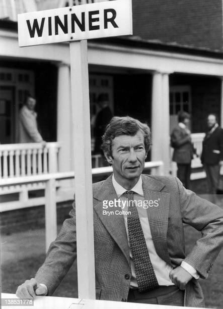 Jockey Lester Piggott poses for a photograph under the 'Winner sign in the winners enclosure at Sandown Park racecourse before riding at the course...