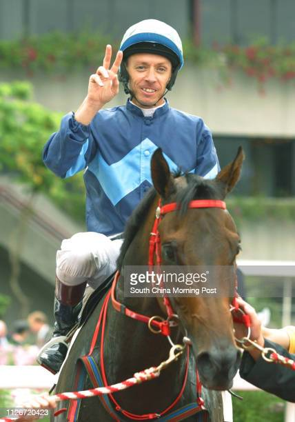 Jockey Michael Cahill shows a victory sign after mounting Solar Empire to win the Race 6 at Sha Tin Racecourse 18 May 2003