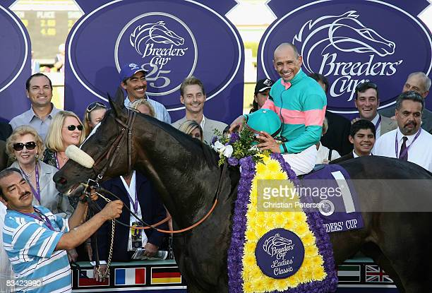 Jockey Mike Smith atop Zenyatta pose with owners and trainers in the winner's circle after winning the Breeders' Cup Ladies Classic during the...