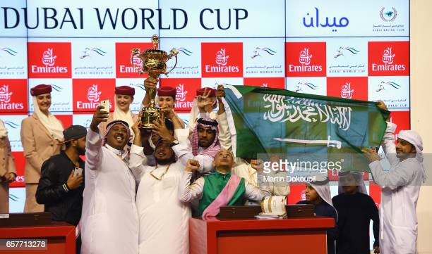 Jockey Mike Smith riding Arrogate celebrates with the trophy after winning the Dubai World Cup Sponsored By Emirates Airline during the Dubai World...