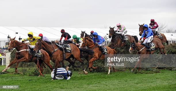 Jockey Nick Scholfield crouches after falling from his horse Teaforthree at The Chair during the Grand National horse race at Aintree Racecourse in...