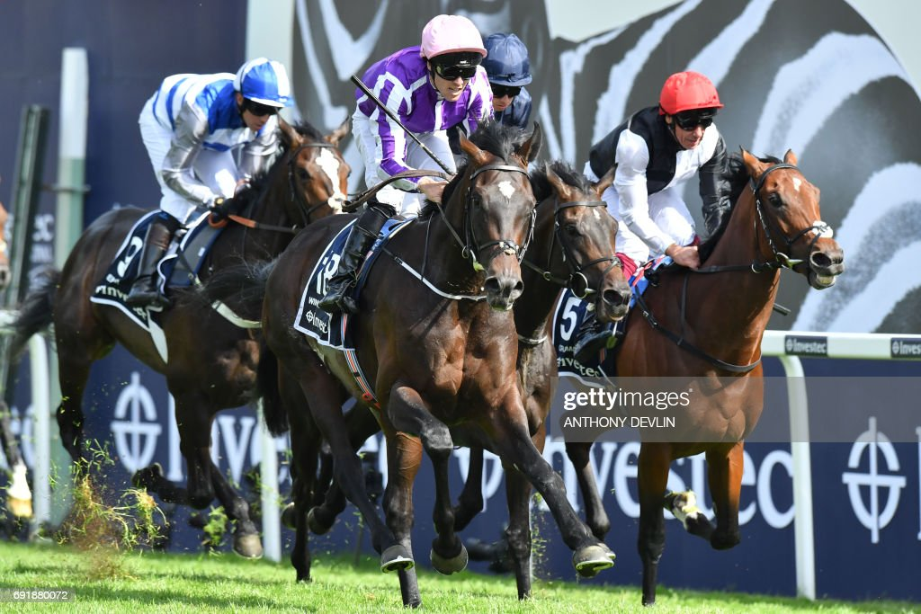 Jockey Padraig Benny (C) rides Wings of Eagles to win the Epsom Derby on the second day of the Epsom Derby Festival in Surrey, southern England on June 3, 2017. / AFP PHOTO / Anthony Devlin