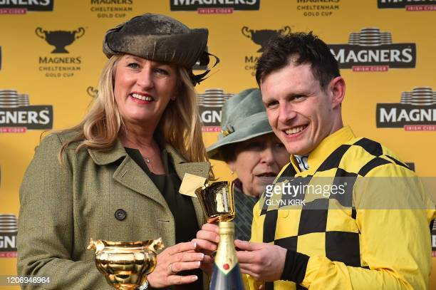 Jockey Paul Townend poses next to the trophy after riding Al Boum Photo to win the Gold Cup race on the final day of the Cheltenham Festival horse...