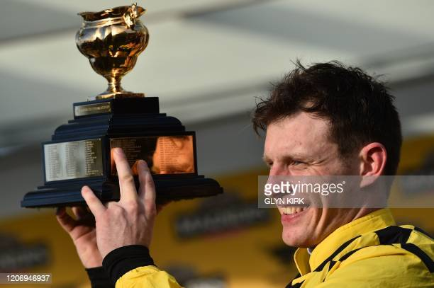 Jockey Paul Townend poses with the trophy after riding Al Boum Photo to win the Gold Cup race on the final day of the Cheltenham Festival horse...