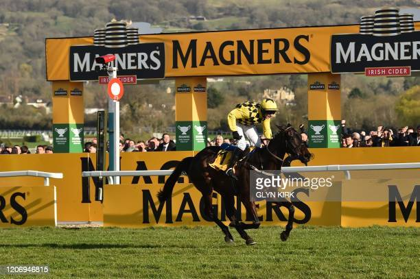 Jockey Paul Townend rides Al Boum Photo as he crosses the finish line to win the Gold Cup race on the final day of the Cheltenham Festival horse...