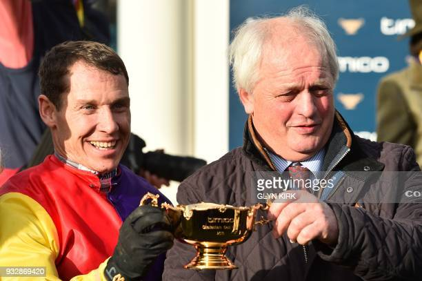 Jockey Richard Johnson and trainer Colin Tizard hold the trophy after Johnson won the Gold Cup race riding Native River on the final day of the...