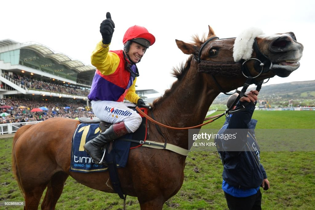 Jockey Richard Johnson celebrates with Native River after winning the Gold Cup race on the final day of the Cheltenham Festival horse racing meeting at Cheltenham Racecourse in Gloucestershire, south-west England, on March 16, 2018. Native River produced a stunning front-running performance to win the Cheltenham Gold Cup and deny trainer Nicky Henderson a historic treble on Friday. Given a brilliant ride by champion jockey Richard Johnson, he and Henderson's favourite Might Bite fought out a thrilling duel throughout the race. / AFP PHOTO / Glyn KIRK