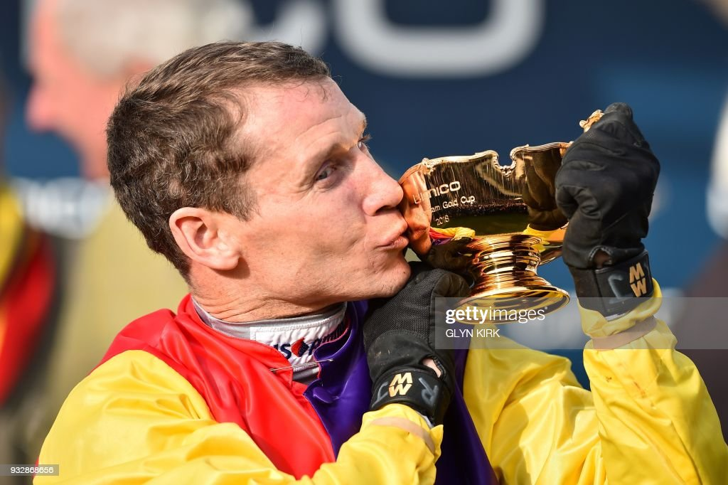 Jockey Richard Johnson kisses the trophy as he celebrates after winning the Gold Cup race riding Native River on the final day of the Cheltenham Festival horse racing meeting at Cheltenham Racecourse in Gloucestershire, south-west England, on March 16, 2018. Native River produced a stunning front-running performance to win the Cheltenham Gold Cup and deny trainer Nicky Henderson a historic treble on Friday. Given a brilliant ride by champion jockey Richard Johnson, he and Henderson's favourite Might Bite fought out a thrilling duel throughout the race. / AFP PHOTO / Glyn KIRK