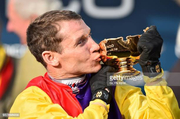 Jockey Richard Johnson kisses the trophy as he celebrates after winning the Gold Cup race riding Native River on the final day of the Cheltenham...