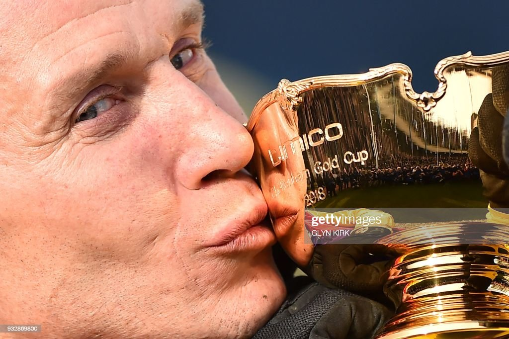TOPSHOT - Jockey Richard Johnson kisses the trophy as he celebrates after winning the Gold Cup race riding Native River on the final day of the Cheltenham Festival horse racing meeting at Cheltenham Racecourse in Gloucestershire, south-west England, on March 16, 2018. Native River produced a stunning front-running performance to win the Cheltenham Gold Cup and deny trainer Nicky Henderson a historic treble on Friday. Given a brilliant ride by champion jockey Richard Johnson, he and Henderson's favourite Might Bite fought out a thrilling duel throughout the race. / AFP PHOTO / Glyn KIRK