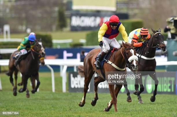 Jockey Richard Johnson on Native River leads jockey Nico de Boinville on Might Bite and jockey Barry Geraghty on Anibale Fly to win the Gold Cup race...