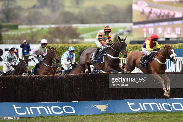 Jockey Richard Johnson on Native River leads jockey Nico de Boinville on Might Bite as they clear a fence on the first lap before going on to win the...