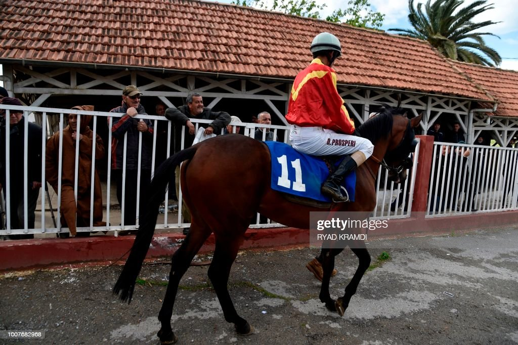 A Jockey Rides Horse Past Onlookers At The Caroubier Hippodrome In Algerian Capital Algiers