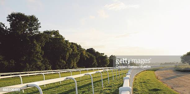 Jockey Riding Horses At Epsom Downs Racecourse Against Sky