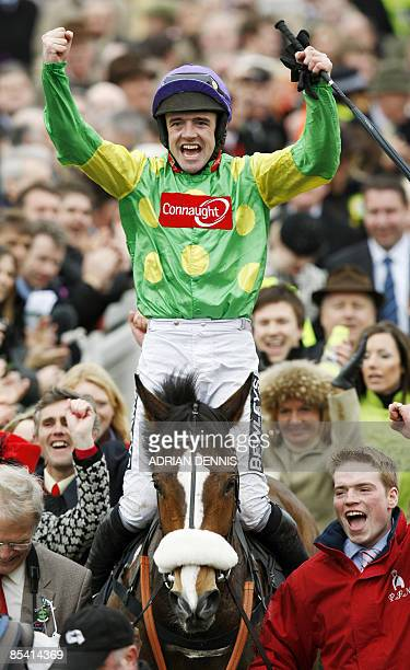 Jockey Ruby Walsh gestures to race-goers as he rides Kauto Star into the Winners Enclosure after winning the Cheltenham Gold Cup during the fourth...