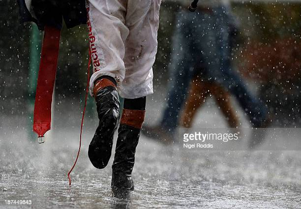 A jockey runs through the rain after The Betfred Nursery Handicap Stakes at Doncaster racecourse on November 9 2013 in Doncaster England