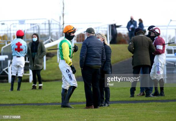 Jockey Ryan Mania has a conversation in the parade ring prior to the beginning of the racingtv.com Handicap Hurdle at Wetherby Racecourse on February...