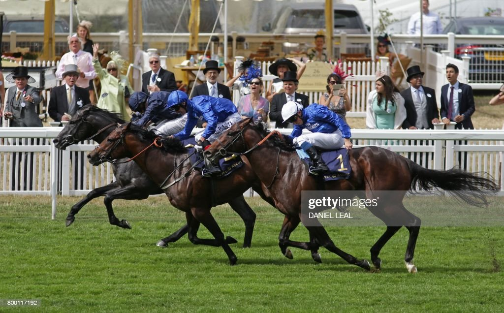 Jockey Ryan Moore on Caravaggio (L) wins the Commonwealth Cup ahead of second placed, Adam Kirby on Harry Angel (C) and third placed, William Buick on Blue Point (R) on the fourth day of the Royal Ascot horse racing meet, in Ascot, west of London, on June 23, 2017. The five-day meeting is one of the highlights of the horse racing calendar. Horse racing has been held at the famous Berkshire course since 1711 and tradition is a hallmark of the meeting. Top hats and tails remain compulsory in parts of the course while a daily procession of horse-drawn carriages brings the Queen to the course. / AFP PHOTO / Daniel LEAL