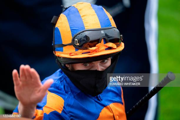 Jockey Ryan Moore reacts in the winner's circle after winning the Oaks Stakes on Love at the Epsom Derby Festival, south of London on July 4, 2020. -...