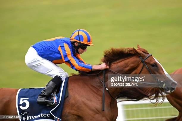 Jockey Ryan Moore rides Love around Tattenham corner on the way to victory in the Oaks Stakes at the Epsom Derby Festival, south of London on July 4,...