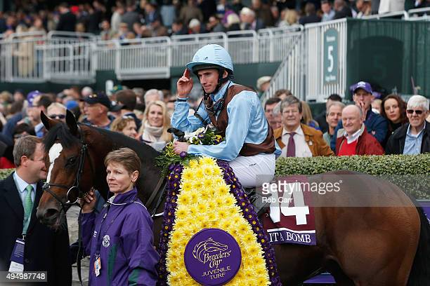 Jockey Ryan Moore tips his hat in the winners circle after riding Hit It A Bomb to win the Breeder's Cup Juvenile Turf at Keeneland Racecourse on...
