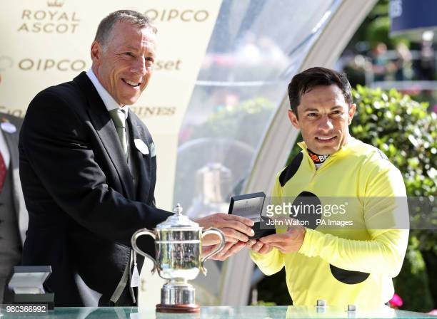 Jockey Silvestre de Sousa is presented an award for winning the Britannia Stakes on Ostilio during day three of Royal Ascot at Ascot Racecourse.
