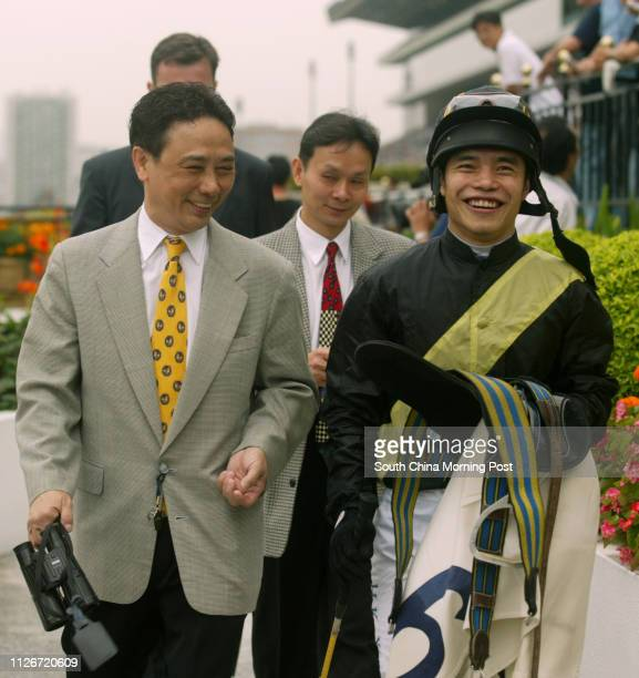 Jockey Simon Yim accompanied by horse trainer Andy Leung returns to scale after mounting racehorse Flying Kenny to win the Race 1 at Sha Tin...