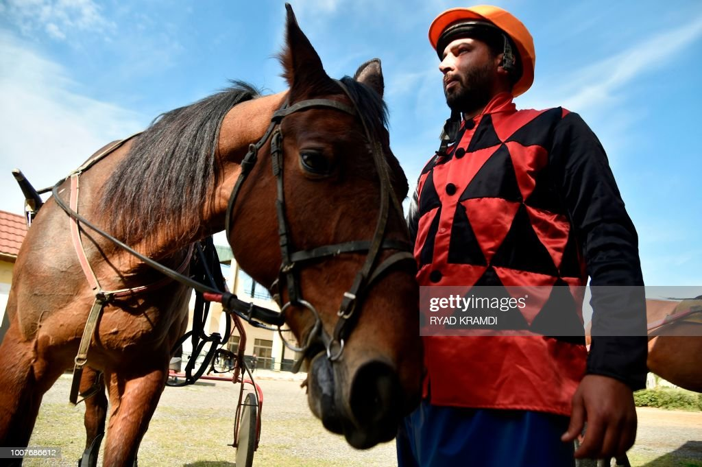 A Jockey Stands Next To His Horse At The Caroubier Hippodrome In Algerian Capital Algiers