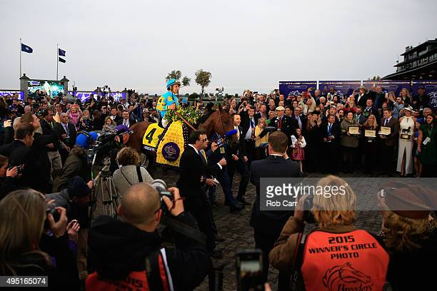 Jockey Victor Espinoza celebrates in the winner's circle after riding American Pharoah to victory in the Breeders' Cup Classic at Keeneland...
