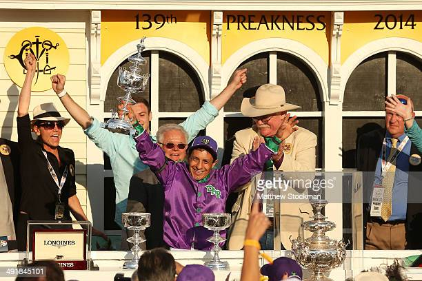 Jockey Victor Espinoza celebrates with owner Steve Coburn and trainer Art Sherman after winning the 139th running of the Preakness Stakes atop...