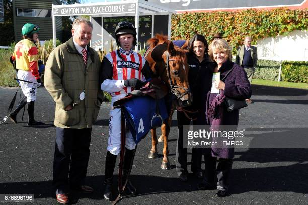 Jockey Wayne Hutchinson with the owners after victory on Jubail in the williamhillcom/mobile Juvenile Hurdle