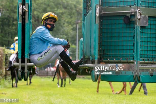 A jockey wearing a face mask waits for the horse at the stalls for the first race of the season in the San Sebastian Hippodrome on June 03 2020 in...
