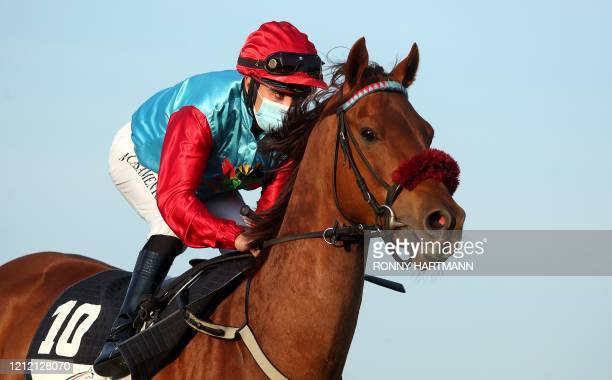 TOPSHOT A jockey wearing a protective mask races on May 7 2020 in Hanover western Germany during the first race meeting in Germany during the novel...