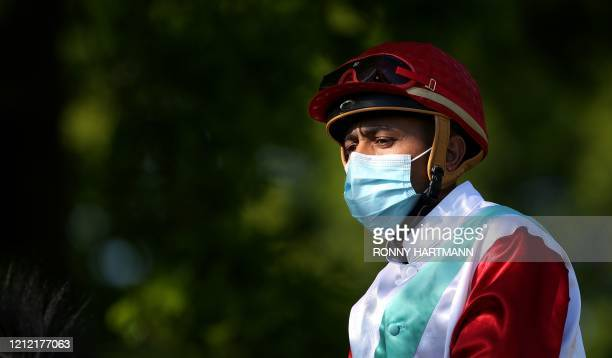 Jockey wears a protective face mask prior to a race at the Neue Bult trotting course in Hanover, northwestern Germany, on May 7 during the first...
