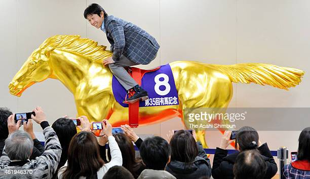 Jockey Yutaka Take rides on the golden statue of racehorse Oguri Cap at the gold crafts exhibition and sale at Kyoto Takashimaya Department Store on...