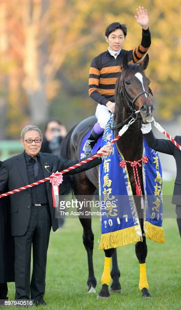 Jockey Yutaka Take riding Kitasan Black pose with owner and singer Saburo Kitajima after winning the 62nd Arima Kinen at Nakayama Racecourse on...