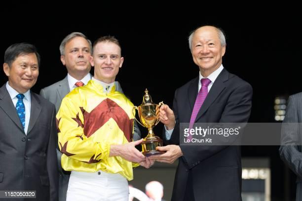 Jockey Zac Purton receives the trophy after Hong Kong runner Southern Legend winning Race 9 Kranji Mile at Kranji Racecourse on May 25 2019 in...
