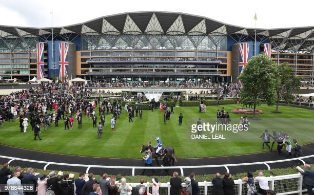 Jockeys and horses are paraded in the parade ring on day one of the Royal Ascot horse racing meet in Ascot west of London on June 19 2018 The fiveday...