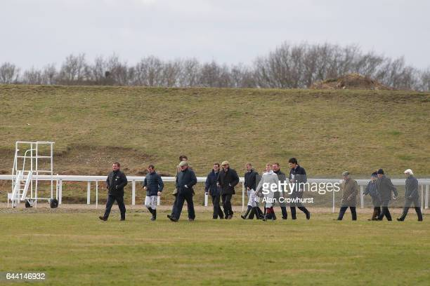 Jockeys and officials return after walking the course to check on the effects of the strong winds at Chelmsford racecourse on February 23 2017 in...