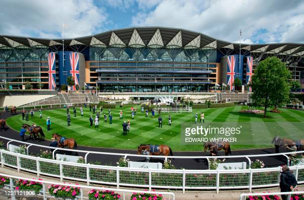 Jockeys and staff stand for the national anthem in the paddock before the Silver Wokingham Handicap on day five of the Royal Ascot horse racing meet,...