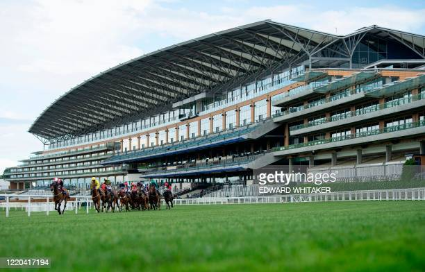 Jockeys and their horses pass the empty stands during the Ascot Stakes race won by jockey Thore Hammer Hansen riding Coeur De Lion on day one of the...