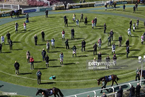 Jockeys and trainers stand for a minutes silence following the announcement of Britain's Prince Philip, Duke of Edinburgh death at the Grand National...