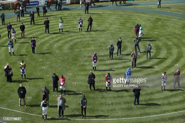 Jockeys and trainers stand for a two minute silence following the death of Britain's Prince Philip, Duke of Edinburgh yesterday on Grand National Day...