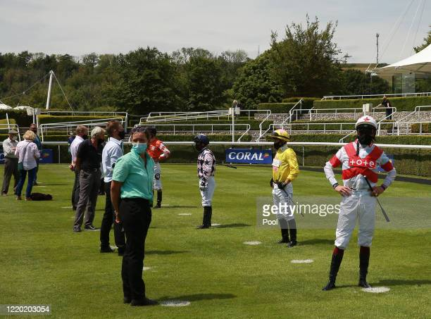 Jockeys are seen social distancing on markers on the grass in the paddock at Goodwood Racecourse on June 15 2020 in Chichester England Photo by Mark...