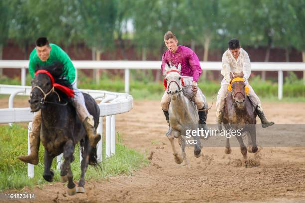 Jockeys compete in a horse racing competition during the 6th Inner Mongolia International Equestrian Festival on July 27, 2019 in Hohhot, Inner...