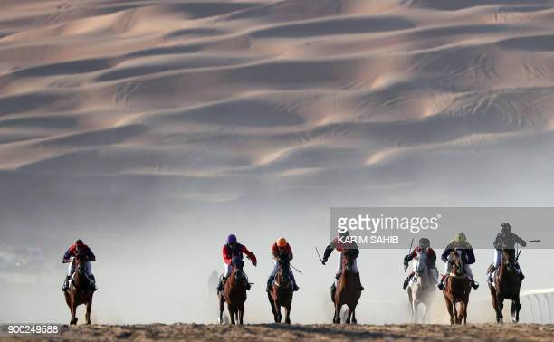 TOPSHOT Jockeys compete in a race for purebred Arab horses during the Liwa 2018 Moreeb Dune Festival on January 1 in the Liwa desert some 250...
