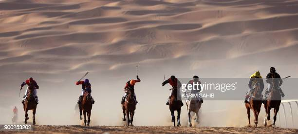 Jockeys compete in a race for purebred Arab horses during the Liwa 2018 Moreeb Dune Festival on January 1 in the Liwa desert some 250 kilometres west...
