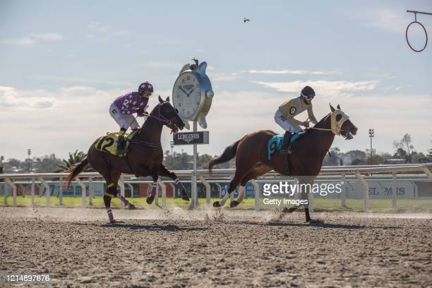 Jockeys Federico Píriz and Hector Lazo compete during the fourth race during competition day as Uruguay slowly returns to normal due to coronavirus...